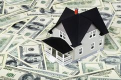 Model of a home on top of hundred dollar bills. Money dollar bill white background paper shape financial Stock Photo