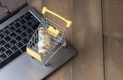 Money Dollar Cash Banknote in Trolley Shopping Cart. On laptop on wood Background, shopping online concept Royalty Free Stock Image