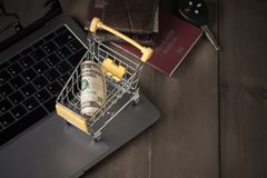 Money Dollar Cash Banknote in Trolley Shopping Cart. On laptop on wood Background, shopping online concept Royalty Free Stock Photography