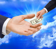 Money Dollar Gift Hand Taxes. A small dollar being handed to a large hand Stock Image