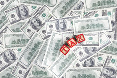 Money dollar and TAX word. Background with money american hundred dollar bills and TAX Royalty Free Stock Photography