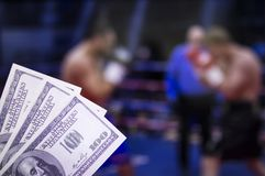 Money dollars against the background of the TV on which show boxing, pugilism stock photography
