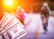 Money dollars on the background of a TV showing cycling, sports betting, cyclotourism. Money dollars on the background of a TV showing cycling, sports betting royalty free stock photography