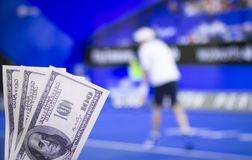 Money dollars on the background of a TV on which the game is shown tennis, sports betting, dollars. Money dollars on the background of a TV on which the game is royalty free stock photo
