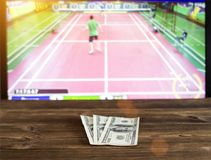Money dollars on the background of TV on which goes badminton, betting office, sports betting. Shuttlecock royalty free stock photos