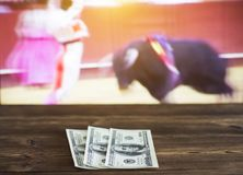Money dollars on the background of a TV on which show bullfight, sports betting, dollars. Money dollars on the background of a TV on which show bullfight, sports Stock Photography