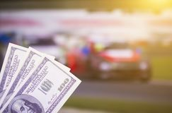 Money dollars on the background of the TV on which show the car rally, sports betting, dollars. Money dollars on the background of the TV on which show the car royalty free stock image