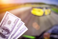 Money dollars on the background of a TV on which show drift on cars, sports betting, money dollars. Money dollars on the background of a TV on which show drift royalty free stock photography