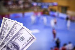 Money dollars on the background of a TV on which show handball, sports betting, money dollars and handball. Money dollars on the background of a TV on which show stock images