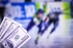 Money dollars on the background of a TV on which show skating sports, sports betting, racing skates dollars. Money dollars on the background of a TV on which stock image