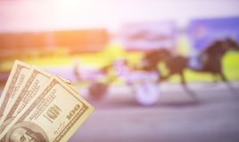 Money dollars on the background of a TV on which show sport trotting, sports betting, bookmaker, dollars. Money dollars on the background of a TV on which show royalty free stock photos