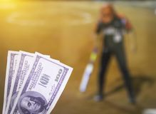 Money dollars on the background of a TV on which show a sports game softball, sports betting, softball. Money dollars on the background of a TV on which show a royalty free stock photography