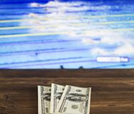 Money dollars on the background of a TV on which show swimming, water sports, sports betting, swimming. Money dollars on the background of a TV on which show royalty free stock images
