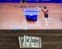 Money dollars on the background of a TV on which show table tennis, sports betting, dollars. Money dollars on the background of a TV on which show table tennis stock photo