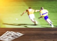 Money dollars on the background of a TV on which the sport is shown in the game of hurling, sports betting, dollars. Money dollars on the background of a TV on stock images