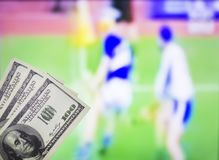 Money dollars on the background of a TV on which the sport is shown in the game of hurling, sports betting, dollars. Money dollars on the background of a TV on royalty free stock image