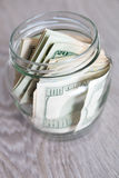 Money. Dollars in open jar on grey wooden background. Royalty Free Stock Images
