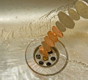 Money down the drain. An image showing a stream of coins entering a sink and drainage hole. Only the drain hole is in focus so the coinage is less specific to a stock image