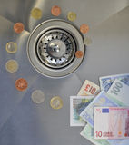 Money down the drain. Notes and coins leading toward plughole illustrating money wastage Stock Photo