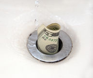 Money down the drain. Five dollar bill going down the drain with water droplets. Room for copy Stock Image