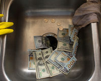 Money down the drain 2. One hundred dollar bills going down the drain Stock Images