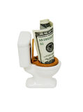 Money down the toilet. Porcelain toilet with wooden seat with money in the form of many large bills Stock Photo