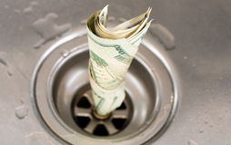 Money drain. US dollars getting flushed down the drain as per th metaphor to waste money stock photo