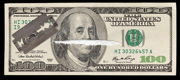 Money and Drugs. A 100 dollar bill with a line of white powder and razor on it Stock Images