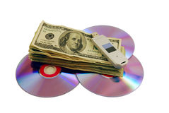 Money and DVDs. Money in the form of many large bills with A couple of purple dvds with red interiors and USB drive Stock Images