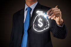 Money earning concept. Chest view of businessman drawing money bag on screen Royalty Free Stock Image