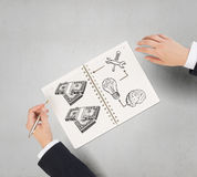 Money earning instruments. Businessman hands drawing money making formula in notepad Stock Image