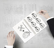Money earning instruments. Businessman hands drawing money making formula in notepad Royalty Free Stock Photos