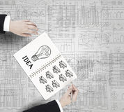 Money earning instruments. Businessman hands drawing money making formula in notepad Royalty Free Stock Images