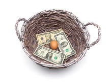 Money and an egg in the basket  on a white background Royalty Free Stock Image