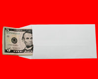 Money Envelope. Five dollar US bills in a white bank envelope. Isolated on red for easy background removal or change Stock Photo