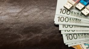 Money in an envelope on a brown leather notepad stock photo