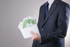 Money in an envelope in the hands of businessman. On gray background Stock Image