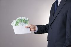 Money in an envelope in the hands of men. On gray background Royalty Free Stock Images