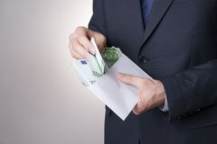 Money in an envelope in the hands of men Stock Images