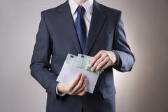 Money in an envelope in the hands of men Stock Photo