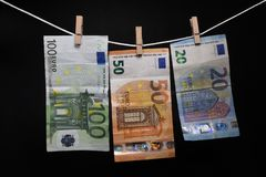 Money. Euro banknotes hanging on rope attached with clothes pins. Money laundering concept on black background stock image