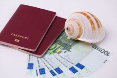 Money EURO banknotes and two passports and a seashell on a white background. Concept money for travel. Money EURO banknotes and two passports and a seashell on Stock Photo