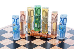Money euro on chess board and Defeated figure of the king. Stock Photo