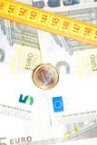 Money euro coin on banknotes near measure tape Stock Images