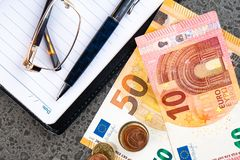 Money euro, notebook and pen on stone background. Bancnots stock photos