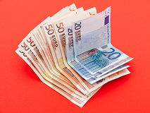 Money - euro notes over red. Wad of Italian Euro notes on red - maybe symbolic of debt - textured background Royalty Free Stock Photography