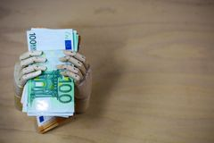 Money , euros in a hand, on wooden background Royalty Free Stock Photos