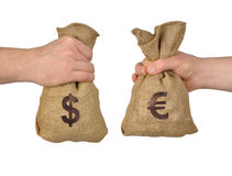Money exchange. Hands exchanging bags with dollars and euro stock image