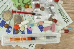 Money for expensive treatment. Money and pills. Pills of different colors on money. Genuine euro banknotes. Stock Image