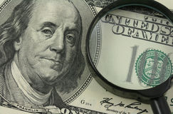 Money expertise. Magnifying glass and fragment of one hundred dollar bill with portrait of president Benjamin Franklin Stock Photos